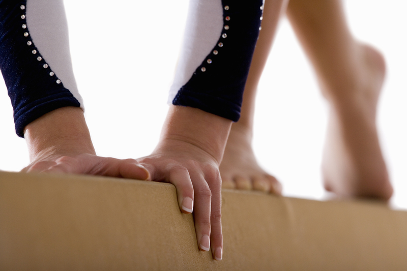 Female gymnast performing on balance beam, close-up, low section.