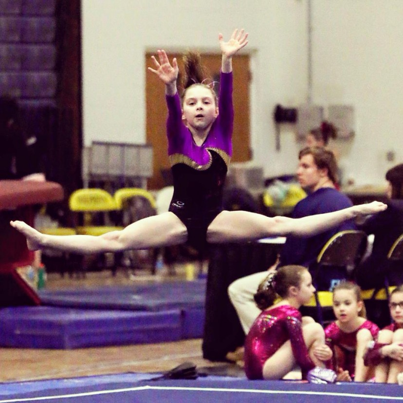 little gymnast doing straddle jump