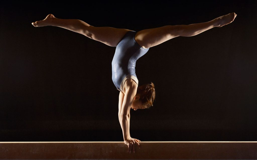 Gymnast doing a handstand on beam