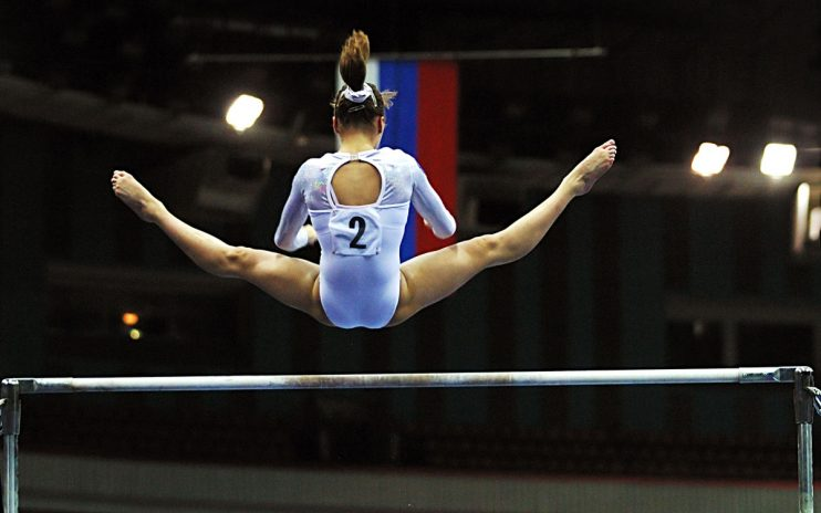 Gymnast doing bar event on competition